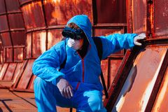 Man environmental mask fire pack disguise facemask bitmask protective overall blue orange rast plant factory disused catastrophe. Men in blue protective overall stock image