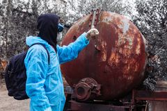 Man environment mask drum pack disguise facemask water muddy protective overall blue rast plant factory disused catastrophe. Men in blue protective overall at stock photography