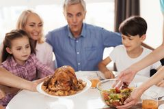 Turkey for Thanksgiving. Family preparing for a festive dinner meeting at the table Royalty Free Stock Photo
