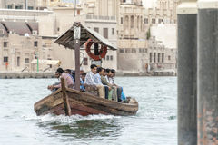 Men on board of abra water taxi across the Dubai Creek. August 2013. People crossing the Creek from Deira to Bur by abra, a traditional wooden water taxi in Stock Image