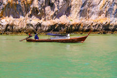 Men on a boat in gul of Thailand. Thai men on a wooden boat in Thailand Stock Image