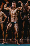 Men bodybuilders in full growth demonstrates  biceps and abdominal muscles Stock Photo