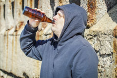 Men with bottle of alcohol near wall Stock Photo