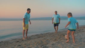 Men and Boy Playing Football on the Beach stock video