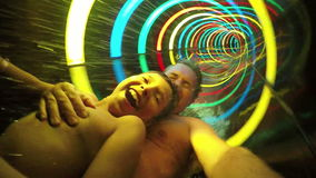 Men and boy ride in rainbow slide stock video footage