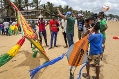 Men and boys inspect a large kite on Negombo beach prior to take off. The kite was one of hundreds to take to the sky above Negombo in Sri Lanka during the Royalty Free Stock Photography