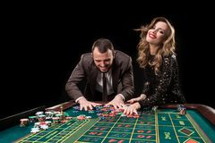 Man and woman playing at roulette table in casino stock photos