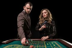 Man and woman playing at roulette table in casino stock images