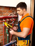 Men builder fixing heating system . Royalty Free Stock Image