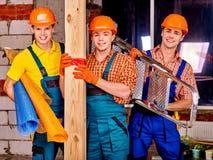 Men in builder uniform. Happy group people men in builder uniform holding wooden boards Royalty Free Stock Photos