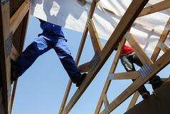 Feet and legs of builders working on a roof stock photo