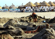 A men is building a huge sand castle on the seaside Stock Images
