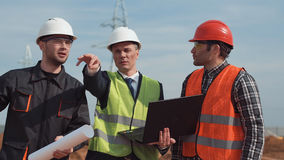 Men on building site discussing the blueprint Stock Image