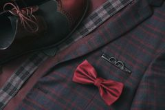 Men burgundy suit, bow tie and vintage leather shoes on  textile tweed background. Wedding accessories Stock Photography