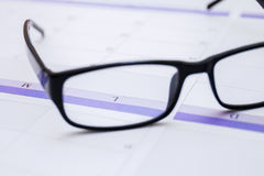 Men business glasses on the table with calendar stock photography