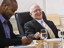 Men in Business Meeting. An elderly man and a young businessman are seated together at a desk in an office.  They are laughing and looking away from the camera Royalty Free Stock Photography