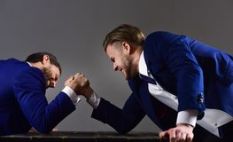 Men or businessmen with tense faces compete in armwrestling. Men in suit or businessmen with tense faces compete in armwrestling on wooden table on dark Royalty Free Stock Photos