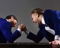 Men or businessmen with tense faces compete in armwrestling. Men in suit or businessmen with tense faces compete in armwrestling on wooden table on dark Royalty Free Stock Photography