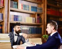 Men with busy faces reading books, studying and drink tea. Intellectuals and aristocrats concept. Men in suits, aristocrats, professors in library or vintage stock image