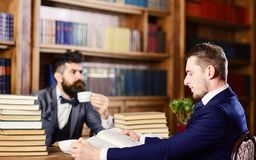 Men with busy faces reading books, studying and drink tea. Men in suits, aristocrats, professors in library or vintage interior with bookshelves on background stock image
