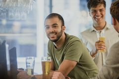 Men Buying Drinks At The Bar. Three men are enjoying drinks at a bar. Two men are talking in the background while one is at the bar, talking to the bar staff royalty free stock photo