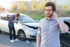 Men calling first aid after a serious car crash Stock Photography