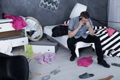 Men calling from messy room. Concerned man sitting on bed in messy room and calling someone royalty free stock image