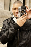 Men with camera. Photo of a young men with a retro camera Stock Photography