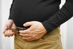 Men can not fasten his belt on  pants due to big stomach Stock Photos