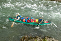 Men in canoe on wild, remote Alaskan river rapids. Two men navigate an overloaded canoe through rapids and rocks during an adventure on a wild Alaskan river Royalty Free Stock Photos