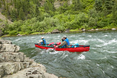 Men canoeing on rough river rapids in wild Alaska. Two men navigate a canoe through rushing, turbulent, rough rapids during an adventure on a river in the Stock Photos