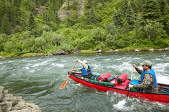 Men canoeing on turbulent river in wild Alaska Royalty Free Stock Photo
