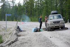 Men and car repair at gravel road Kolyma to Magadan highway at Y Stock Image