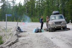 Men and car repair at gravel road Kolyma to Magadan highway at Y Stock Image