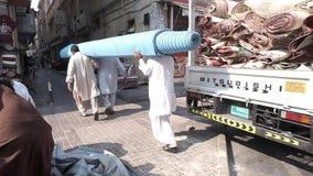 Men carry blue carpet flooring roll along narrow street. Dubai United Arab Emirates - December 18 2018: Arabian men in white dress carry blue carpet flooring stock video footage