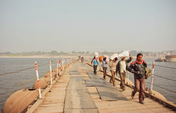 Men carry heavy bags of goods across the bridge over wide river Ganges Royalty Free Stock Image