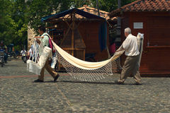 Men carrying  a hammock for sale Royalty Free Stock Photos