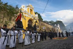 Men carrying parade floats in a street of the old city of Antigua during a procession of the Holy Week, in Antigua. Antigua, Guatemala - April 19, 2014: Men stock photos