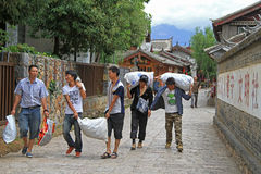Men are carrying sacks in Lijiang Royalty Free Stock Image