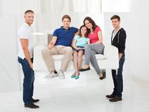 Men carrying sofa with a family Stock Photography