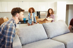 Men Carrying Sofa Helping With Move Into New Home Stock Image