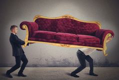 Men carrying a sofa. Men carrying a very heavy antique sofa Royalty Free Stock Photo