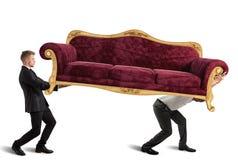 Men carrying a sofa. Men carrying a very heavy antique sofa Stock Photography