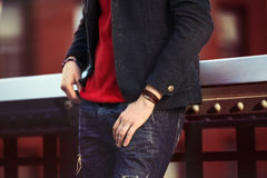 Men casual street style clothes with jeans, jacket. Red pullover and wristband Stock Photo