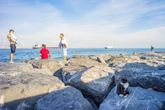 Men and Cat on Rocks at Bosphorus Bank Stock Photo