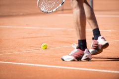 Men catchs up tennis ball on range sand Royalty Free Stock Photos