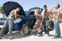 Men changing a wheel. Under the sun stock photos
