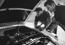Men Checking Broke Down Car on Street Side with Open Hood Royalty Free Stock Image