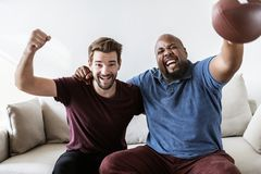 Men cheering sport together at home Stock Photos