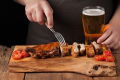 Men chef skewers with a fork ready to eat pork ribs, lying on an old wooden table. A man tries to snacks and drinks of light beer. On black background Royalty Free Stock Photos